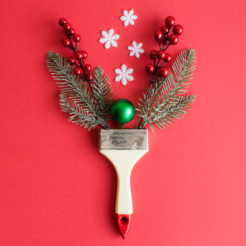 Flat lay of paint brush with christmas tree branches, bauble decoration, snowflakes and red berries minimal creative holiday concept.
