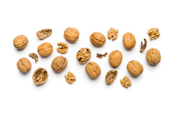 top view of walnuts closed and broken scattered on a white background with copy space Fotomurales