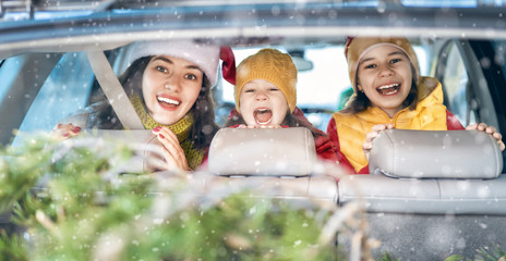 Mother, children and car on snowy winter nature