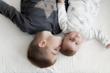 children lie on the bed and interact with each other.