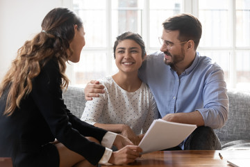 Financial advisor consulting diverse young family couple about deal.