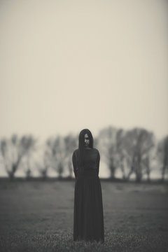Girl in a long dress on the background of a gloomy forest black and white photo . A woman in a dark forest scary atmosphere like in a horror movie. An image of a girl from a Halloween horror movie.