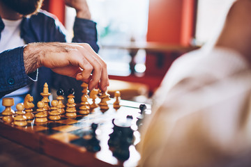 Cropped image of male hands making move of white pawn on wooden chessboard during strategic game in chess sitting in coworking.Selective focus on sport battle in tactic play with chess