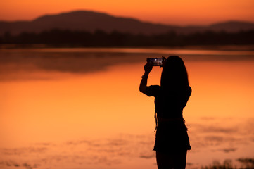 Silhouette Asian girl taking a photo by her mobile at tourist attractions in sunset,Sakonnakhon,Thailand.
