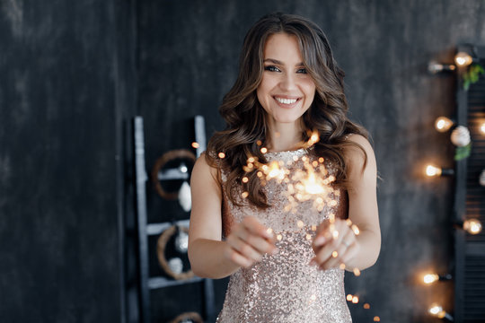 Girl with a sparkler near the Christmas tree. A cheerful young woman with a cute smile in a beige dress is standing and holding a sparkling sparkler in the hands against the background of the Christma