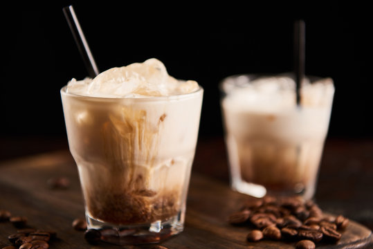 selective focus of white russian cocktail in glasses with straws on wooden board with coffee grains isolated on black