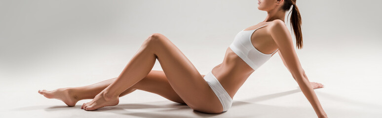 side view of beautiful slim woman in underwear sitting on grey background, panoramic shot