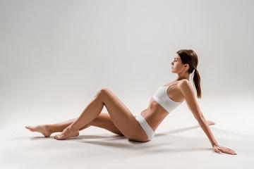 side view of beautiful slim woman in underwear sitting on grey background