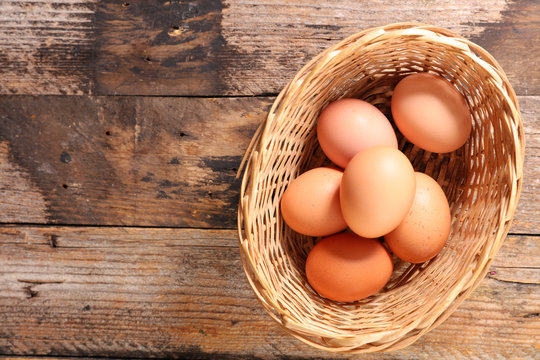 raw egg in box on wood background