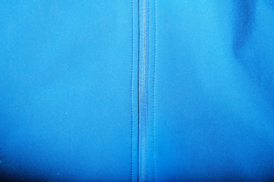 Detailed view of softshell jacket with water drops, zipper and seams. blue background