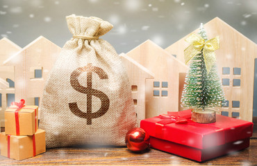 Money bag, wooden houses, Christmas tree and gifts. Holiday discounts. Christmas sale of real estate. New Year discounts for buying housing. Purchase apartments at a low price. Favorable prices