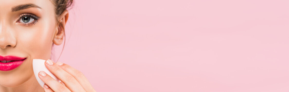 cropped view of naked beautiful woman with pink lips holding makeup sponge isolated on pink, panoramic shot