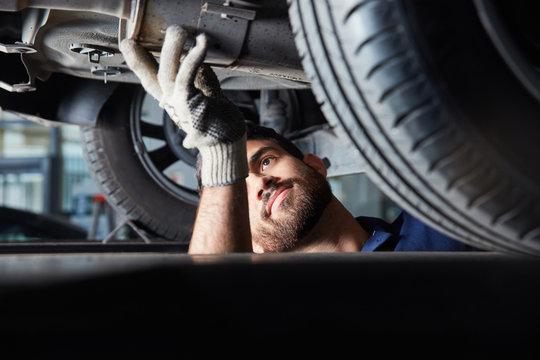 Mechatroniker bei der Reparatur von Auto Auspuff