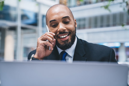 Cheerful businessman in suit having phone call