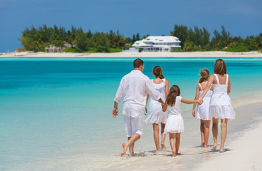Happy Caucasian family in white walking on beach
