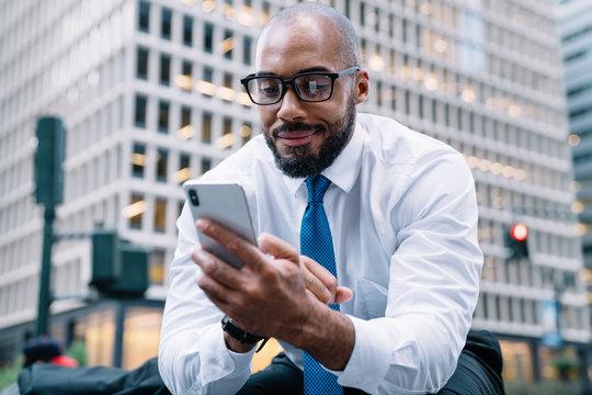 Smiling formal businessman browsing mobile sitting on street stairs