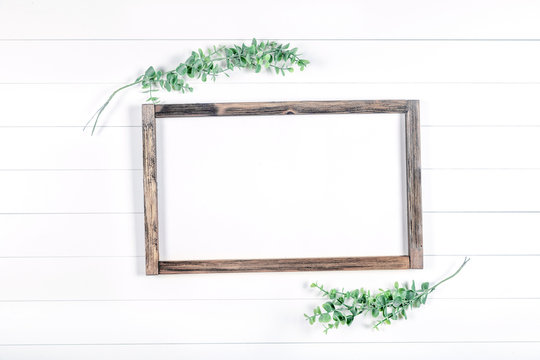 Spring or summer wooden frame mockup with greenery