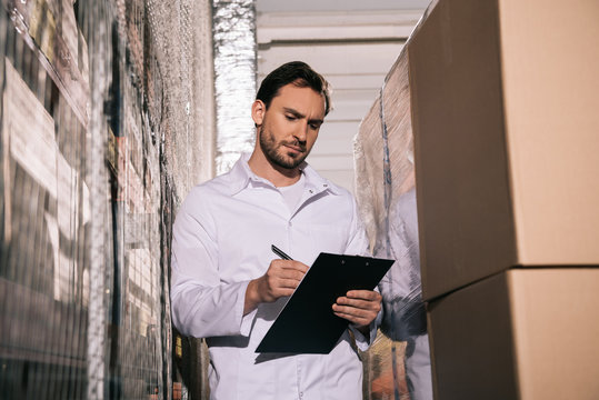 concentrated storekeeper in white coat writing on clipboard in warehouse