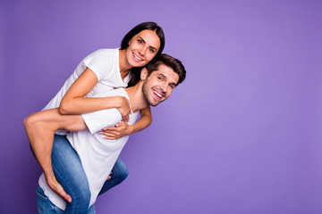 Side profile photo of cute nice charming couple of brown haired people with guy carrying piggyback...