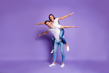 Full length body size photo of cheerful excited positive couple with her riding his back with arms...