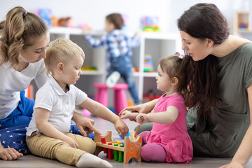 Little toddlers kid boy and child girl with moms playing together in nursery room. Preschool children in day care centre