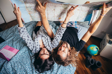 Young couple lying on bed planning travel reading map