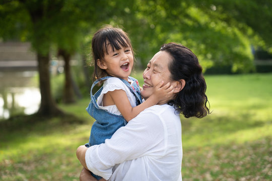 Adorable asian granddaughter is playing and laughing together with grandmother with fully happiness moment in the green park, concept of love and relation of difference generation in family lifestyle