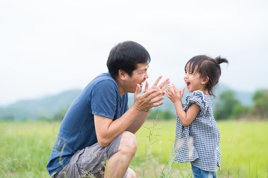 Asian father and daughter are playing and laughing together with fully happiness moment in the background of sky and mountains.