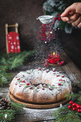 Traditional homemade christmas cake holiday dessert with cranberry and chocolate with new year tree decoration on vintage wooden table background. Rustic style.