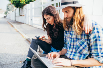 Young beautiful couple sitting outdoor using computer and smartphone