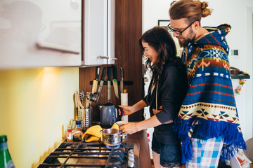 Affectionate young couple cooking food in kitchen at home