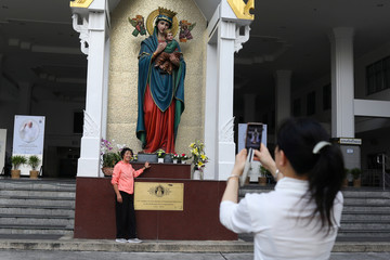 Catholics who traveled from Shanghai to Bangkok to attend mass held by Pope Francis, takes photos with virgin Mary at the Holy Redeemer Church in Bangkok