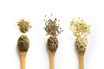 Organic dried hemp seeds, flour, kernels in wooden spoon on white background. View from above.