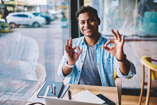 Half length portrait of mature handsome successful businessman having fun during working break in coffee shop.Emotional smiling male person showing ok using fingers while looking at camera in cafe