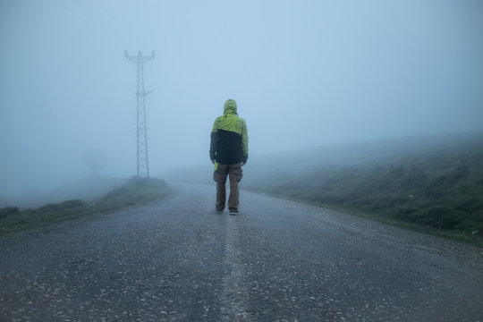 lonely man walking into the unknown in a foggy road with a yellow jacket