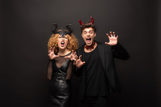 scary young couple posing in halloween costumes on black