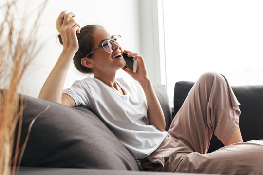 Image of excited nice woman talking on cellphone and holding apple