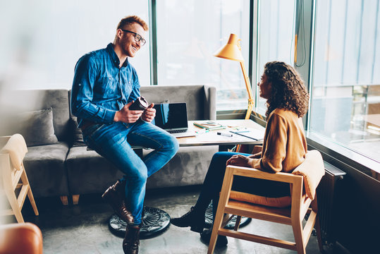 Cheerful young colleagues communicating with each other during working break in studio interior.Two positive male and female employees taking about funny stories sitting in stylish office