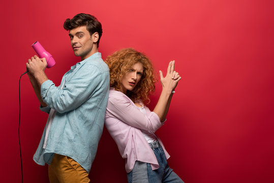 happy couple having fun with hair dryer and hand gun, on red