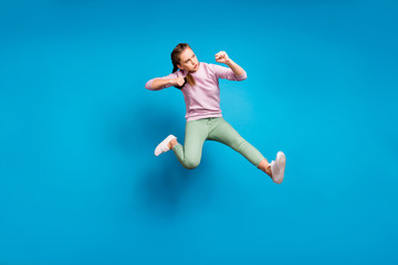 Full body profile side photo of concentrated funky youth girl jump train her fighting skills kick leg enemy wear modern clothes sweater isolated over blue color background Wall mural