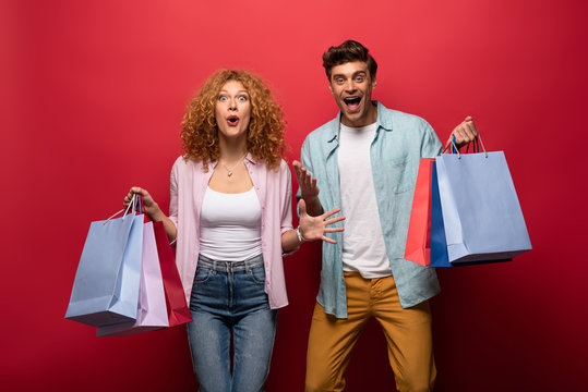 excited beautiful couple holding shopping bags, isolated on red