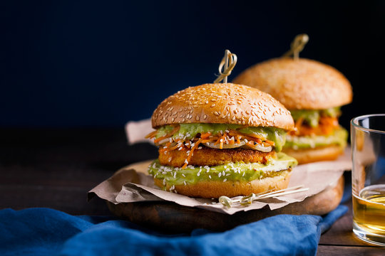 Vegan sweet potato chickpea burgers with avocado guacamole sauce and carrot slaw on dark blue background with copy space for text.Vegetarian meal,plant based food concept.Horizontal orientation