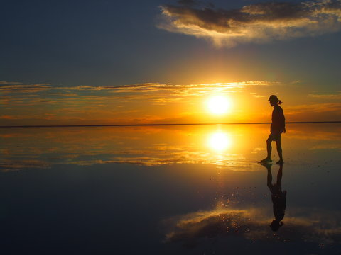Groom backlit by a beautiful sunset, the groom is standing on a salt lake with the landscape reflected, Salar de Uyuni, Salar de Uyuni is the world's largest salt flat, Bolivia