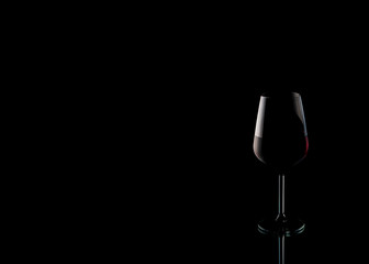 Spoed Foto op Canvas Alcohol glass with red wine on a black background with beautiful highlights on the mirror table.