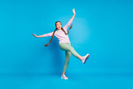 Caution. Slippery floor. Full length photo of frightened girl go walk slip fall down scream omg raise leg hands feel panic wearing casual style outfit isolated over blue color background