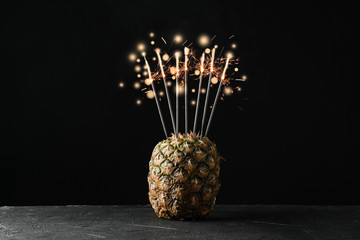 Pineapple with burning sparklers on black background, space for text