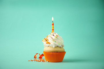 Delicious birthday cupcake with candle on light green background