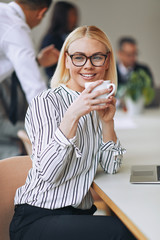 Smiling young businesswoman sitting at work drinking a coffee