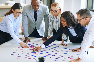 Diverse group of businesspeople working together to solve a puzz