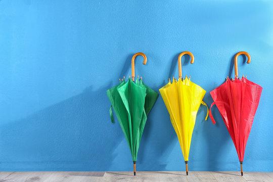 Beautiful closed colorful umbrellas near blue wall